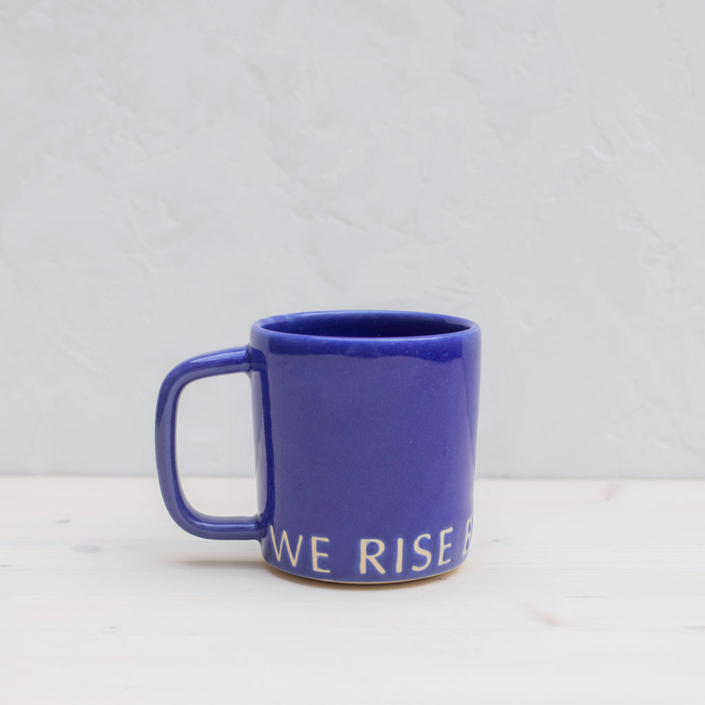 We Rise By Bowing Mug