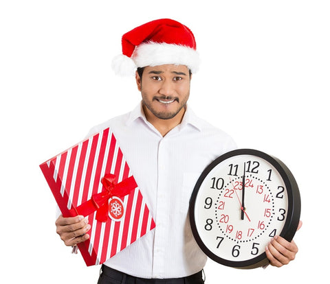 Closeup portrait of worried young man wearing red santa claus hat, holding clock and gift in hands, isolated on white background. Negative emotion facial expression. Last minute christma
