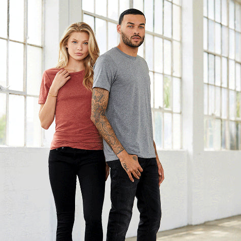 A woman and a man in custom Bella + Canvas custom t-shirts and black pants standing in a white room with windows