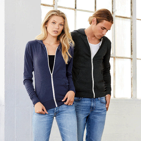 A woman in a blue custom Bella + Canvas zip-up hoodie and a man in a black corporate Bella + Canvas hoodie in front of a white room