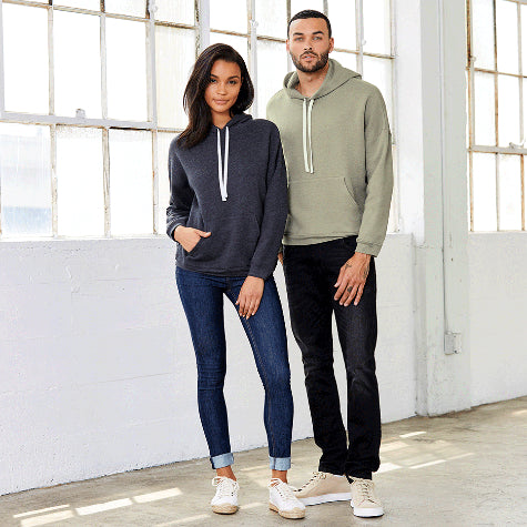 A woman and man standing in front of white windows with custom Bella + Canvas hoodies on