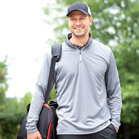 A man walking on a golf course is wearing a corporate Puma Golf zip-up jacket for men