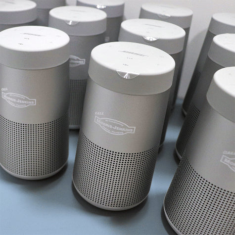 Corporate Bose speakers with a custom company logo printed on the front from Merchology