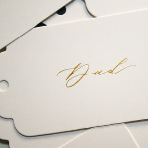 White and gold calligraphy place card tags from Sam's Little Studio, London