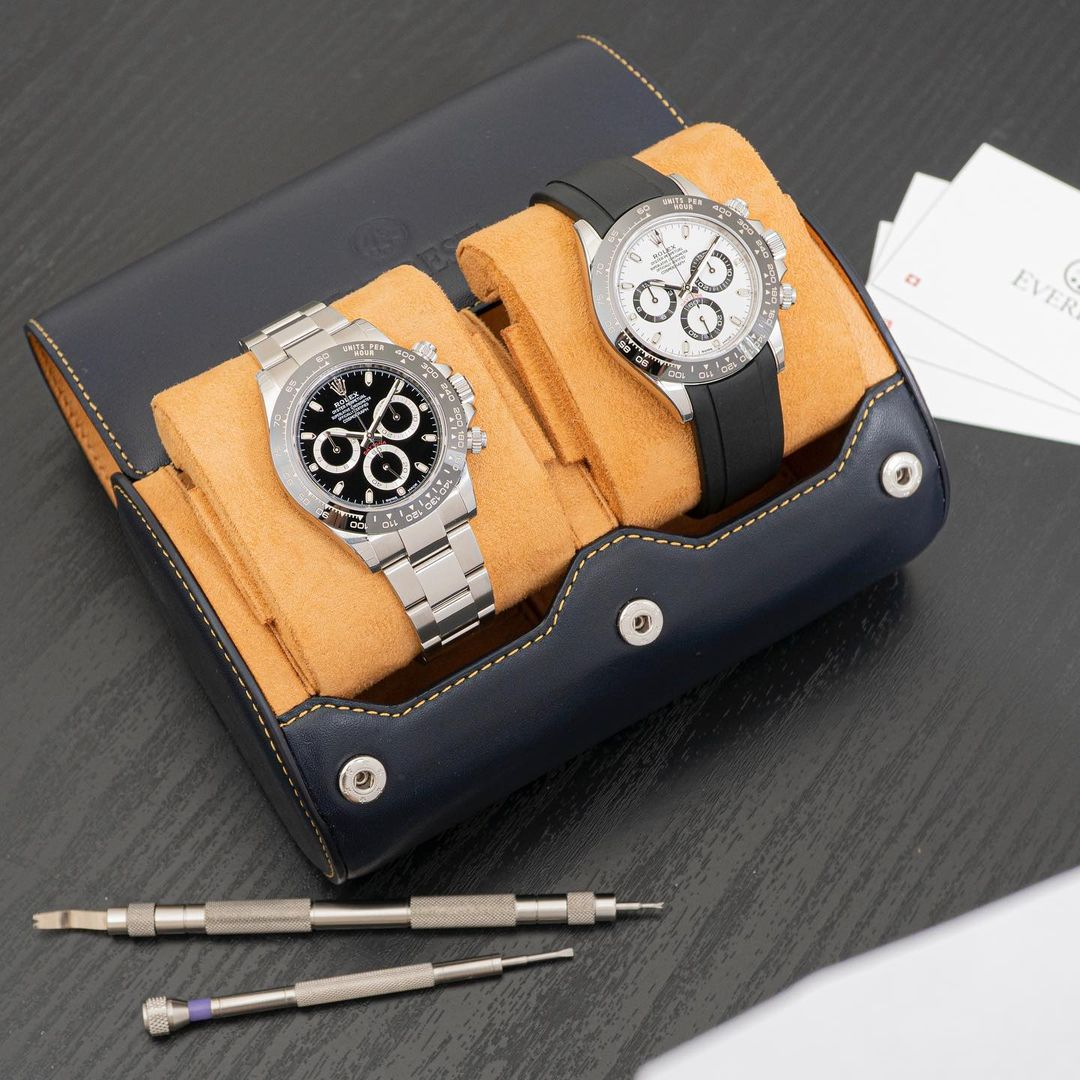 navy blue leather watch roll with rolex watches inside and a tool kit nearby