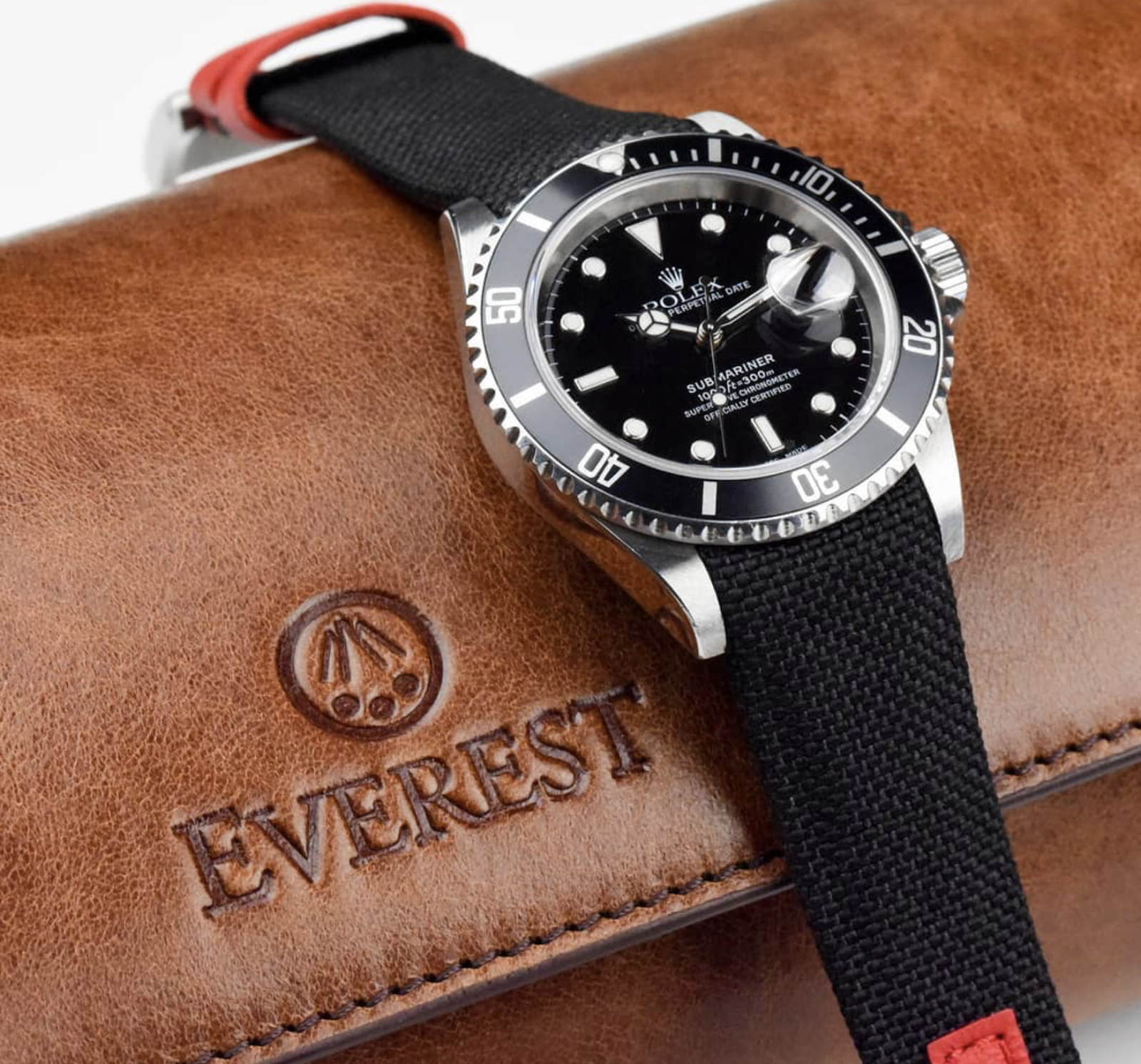 curved end nylon strap on rolex submariner next to a leather watch roll