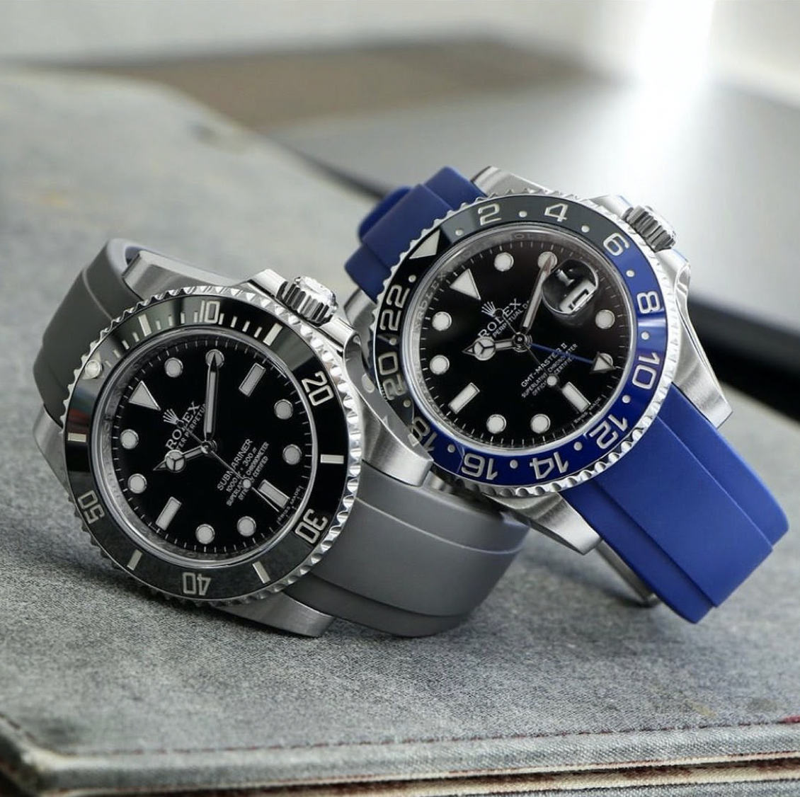 two rolex watches one with gray rubber and one with blue rubber everest bands