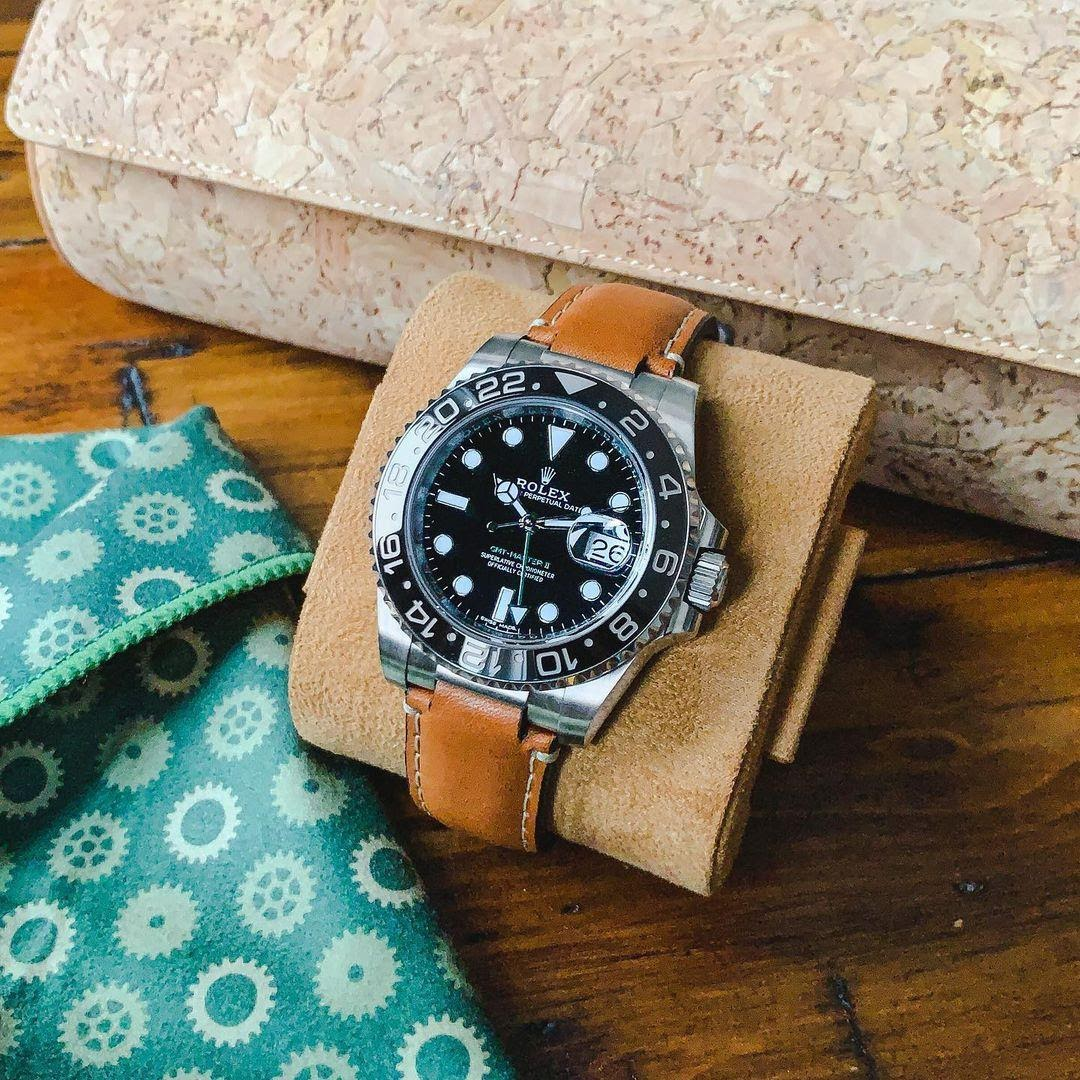 rolex watch on curved end leather strap next to a cork everest watch roll