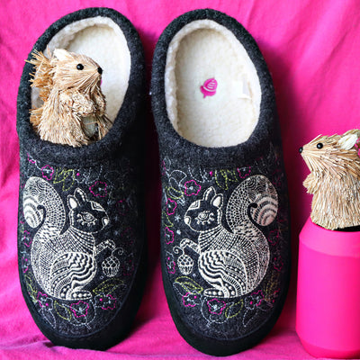 Women's Forest Mule gray squirrel Slippers sitting on pink fabric with squirrel wood figures