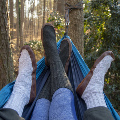 The Original Slipper Sock in Charcoal and Light Gray On Male and Female Models Sitting in Hammock