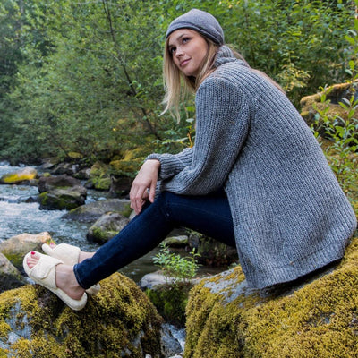 Women's Spa Slide Slippers in Natural On Model Sitting on River Rocks and Moss