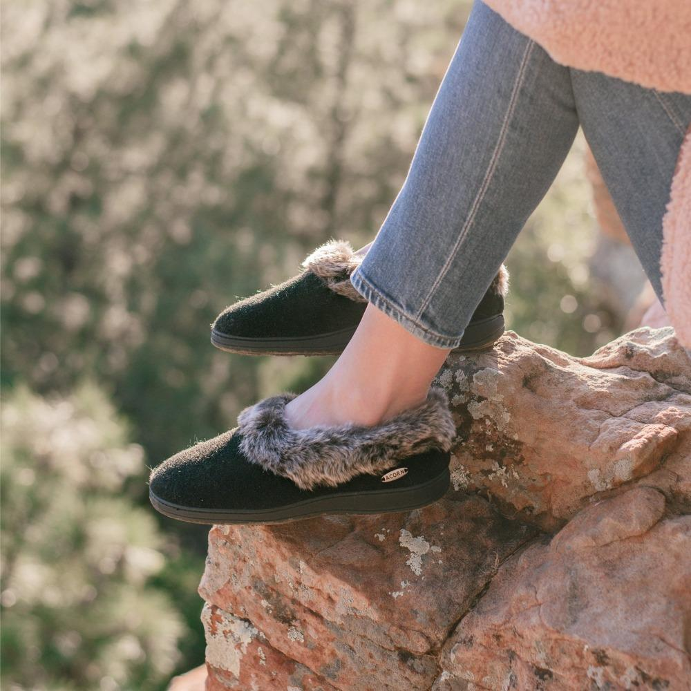 Women's Faux Fur Collar Slippers in Black on Model Sitting on a Rock While Hiking