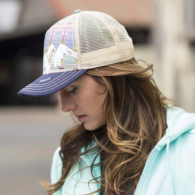 Lady wearing Pistil McKinley Trucker Hat displaying a colorful Mountain with mesh back and adjustable closure in Aqua