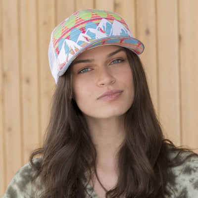 Lady wearing Pistil McKinley Trucker Hat displaying a colorful Mountain with mesh back and adjustable closure in Persimmon