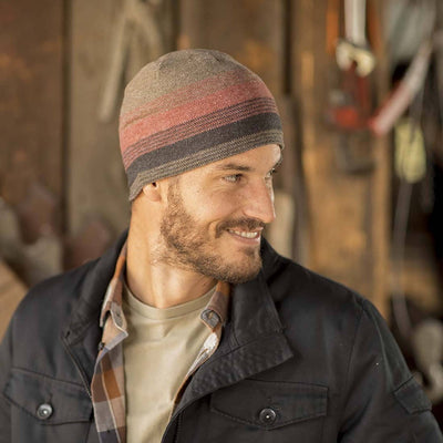 Gentleman wearing Pistil Chase Fine Gauge Knit Beanie with colorblocked stripes in red and brown