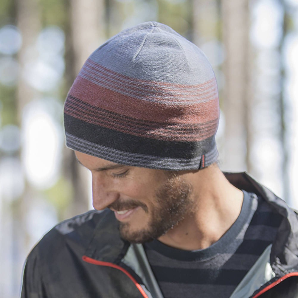 Gentleman wearing Pistil Chase Fine Gauge Knit Beanie with colorblocked stripes in orange black and grey looking down