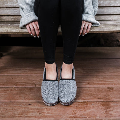 Women's Woven Trim Moccasins in Stormy Grey on model sitting on a bench outside