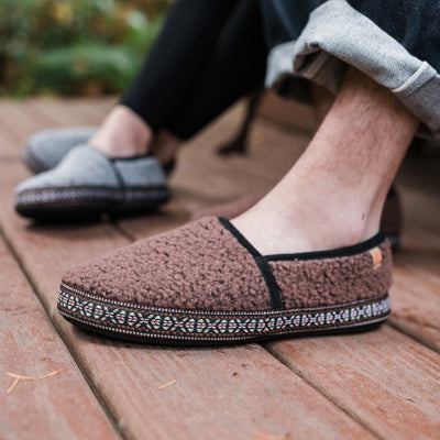 Acorn Men's Woven Trim Moccasin Slipper in Walnut on model with women sitting next to him in matching slippers in Stormy Grey