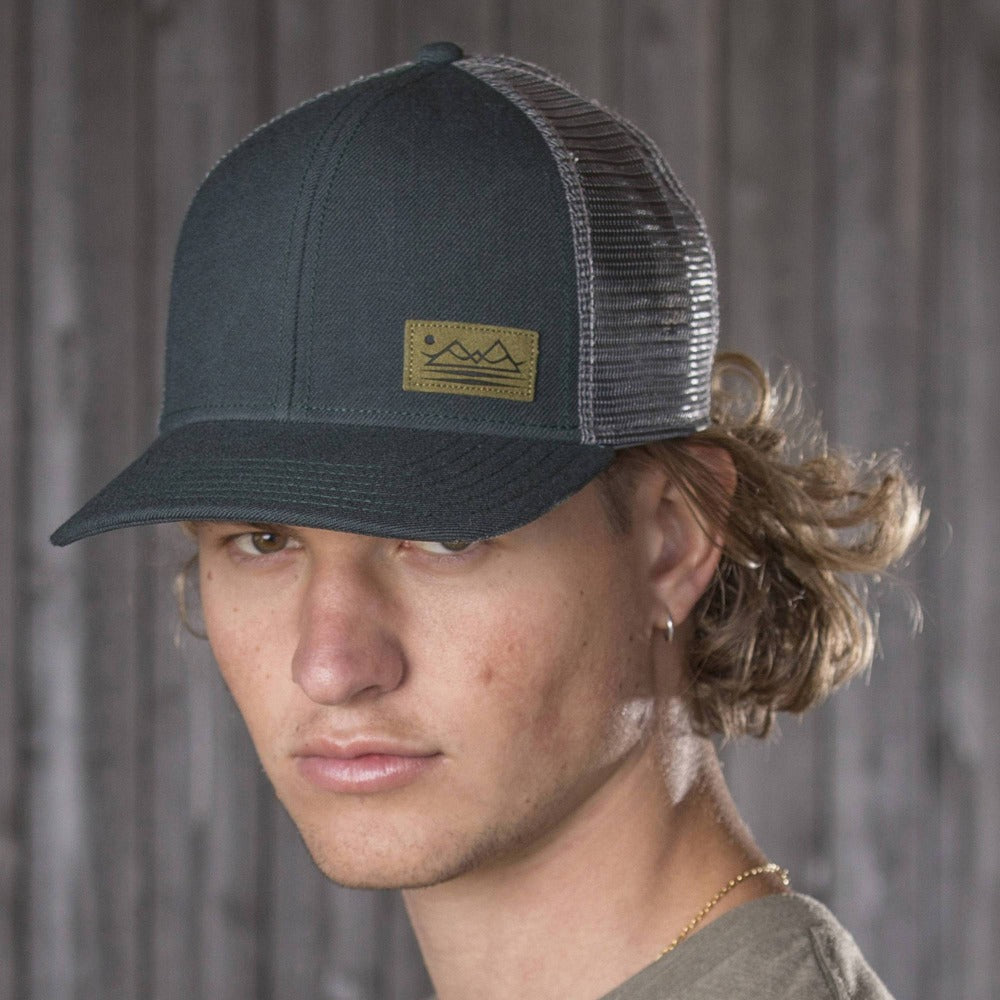 Gentleman Wearing Pistil Dean Trucker Cap with mountain patch mesh back and adjustable closure in Spruce
