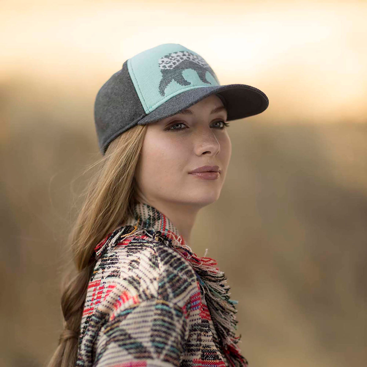 Lady wearing Pistil Ursa Cap with jacquard knit bear graphic front panel in aqua