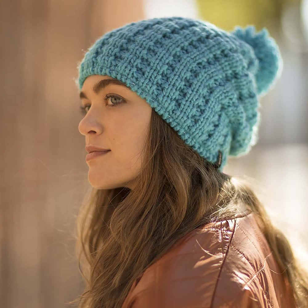 Lady wearing Pistil Tito Chunky Waffle Knit Slouch Beanie with pom in blue