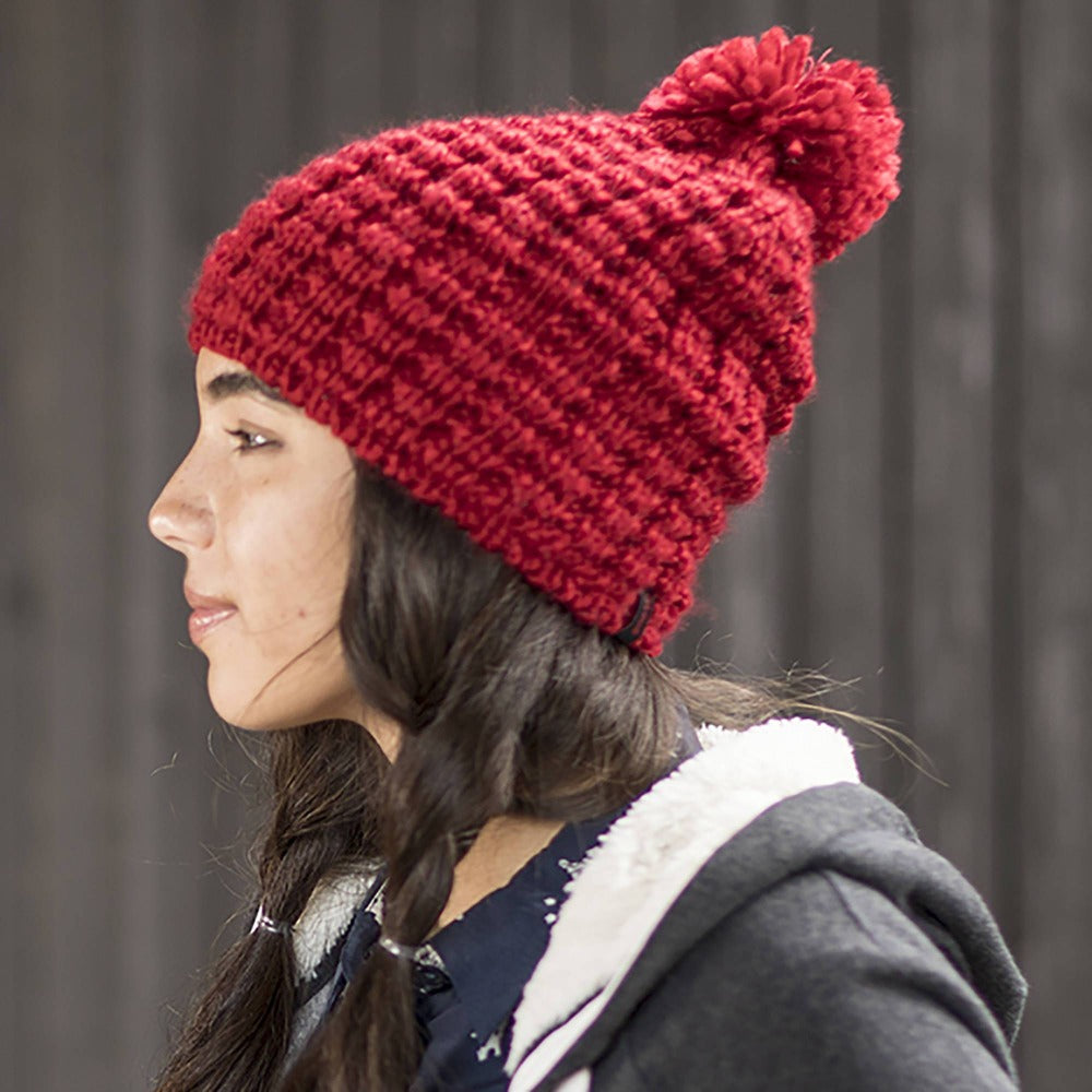 Lady wearing Pistil Tito Chunky Waffle Knit Slouch Beanie with pom in red