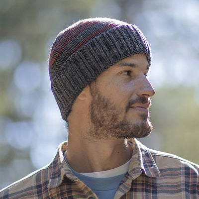 Gentleman wearing Pistil Perch Knit Beanie with grey band and orange stripes