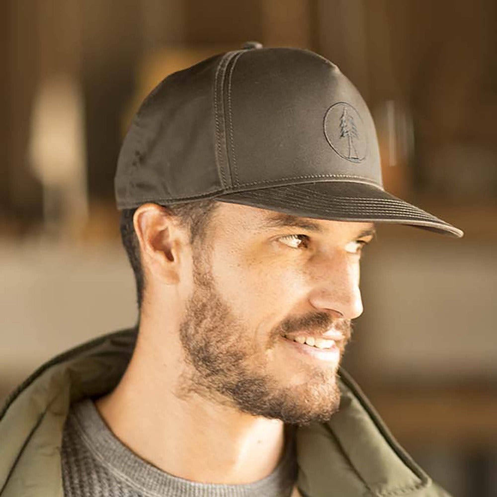 Gentleman wearing Pistil Timber Trucker Cap with fir tree embroidered on front panel and adjustable closure in the back in Brown