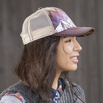 Lady wearing Pistil Trucker Hat with a Colorful Mountain Scene adjustable closure and mesh back in brown