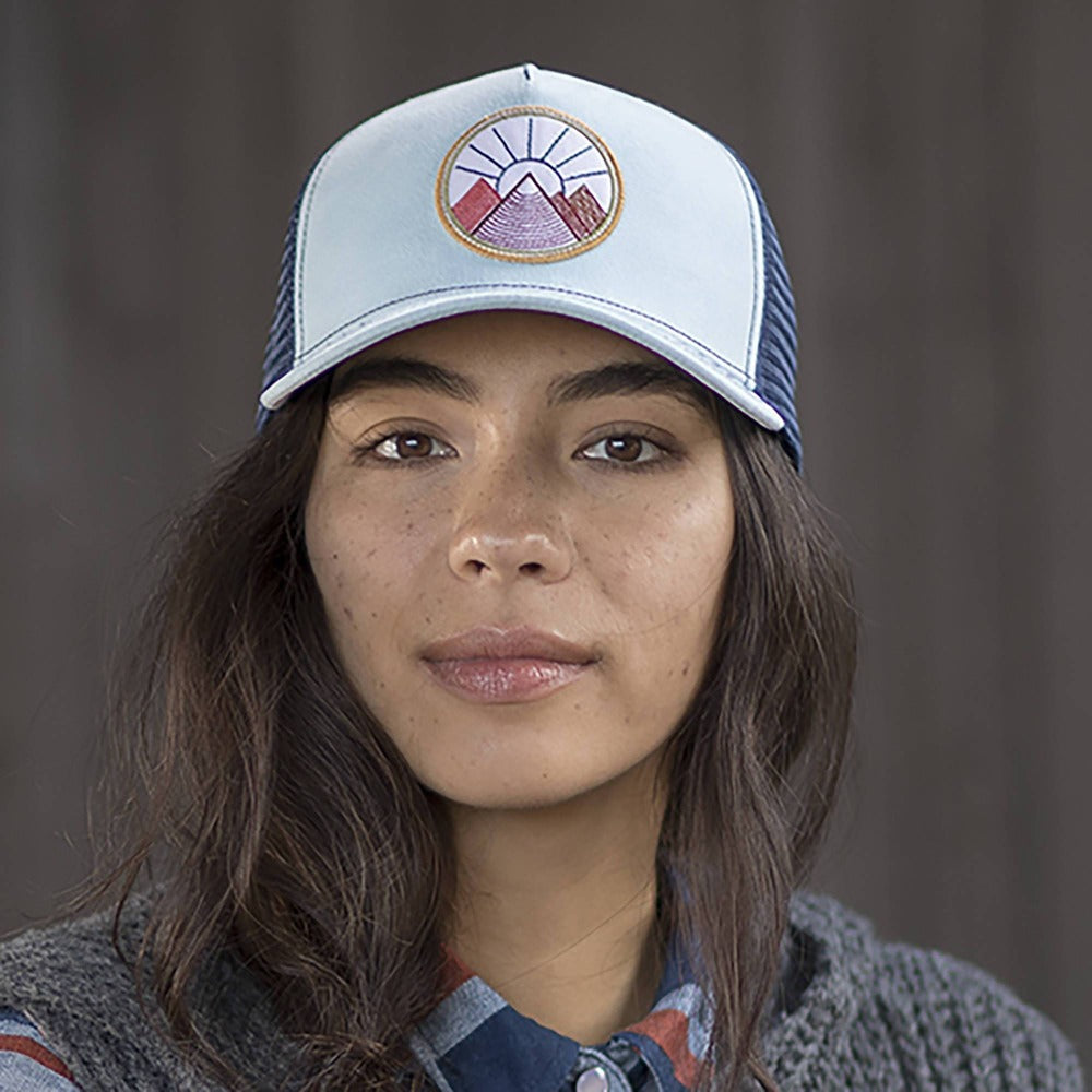 Lady wearing Pistil Viva Trucker Hat with Mountain and Sun Embroidered on round patch, mesh back, adjustable closure in Sky