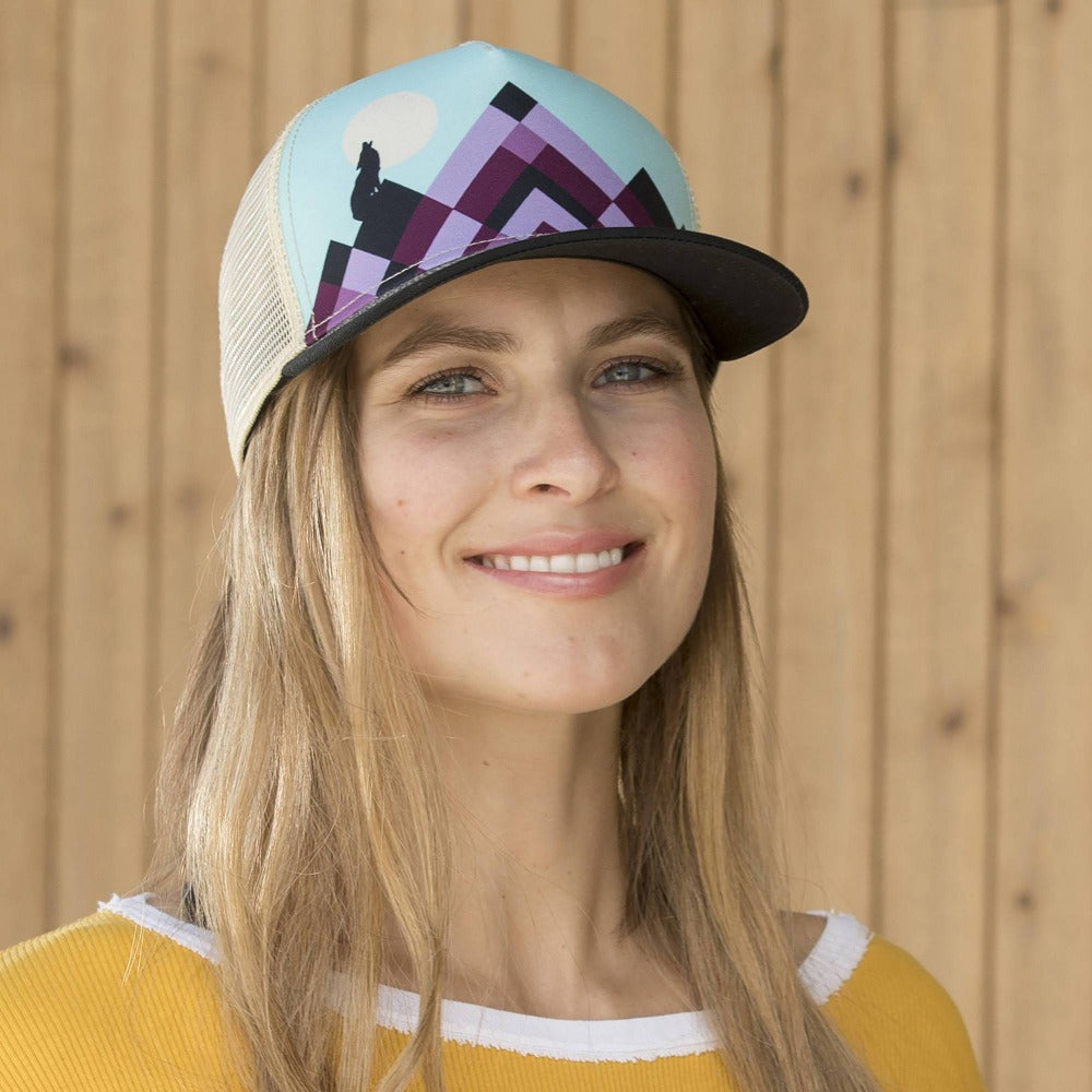 Lady wearing Pistil Lunar Trucker Hat with purple mountain on blue background and black bill mesh back and adjustable closure