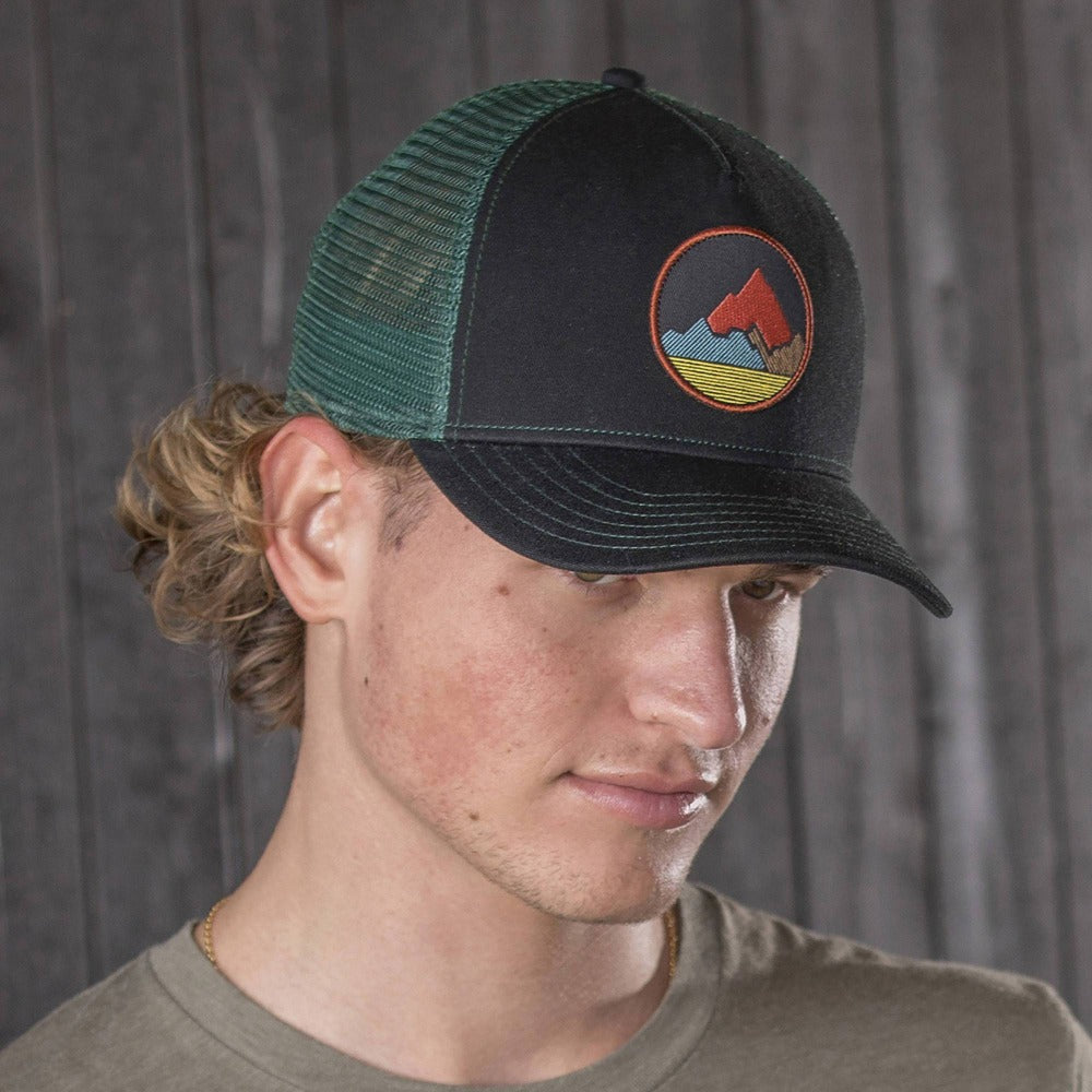 Gentleman wearing Pistil Spike Trucker Cap with embroidered Mountain badge, mesh back, adjustable closure in Black