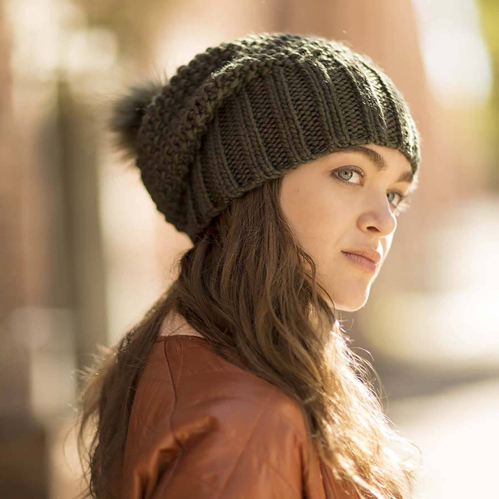 Lady wearing Pistil Juliette Slouch Style Knit Beanie with Pom in Olive side shot