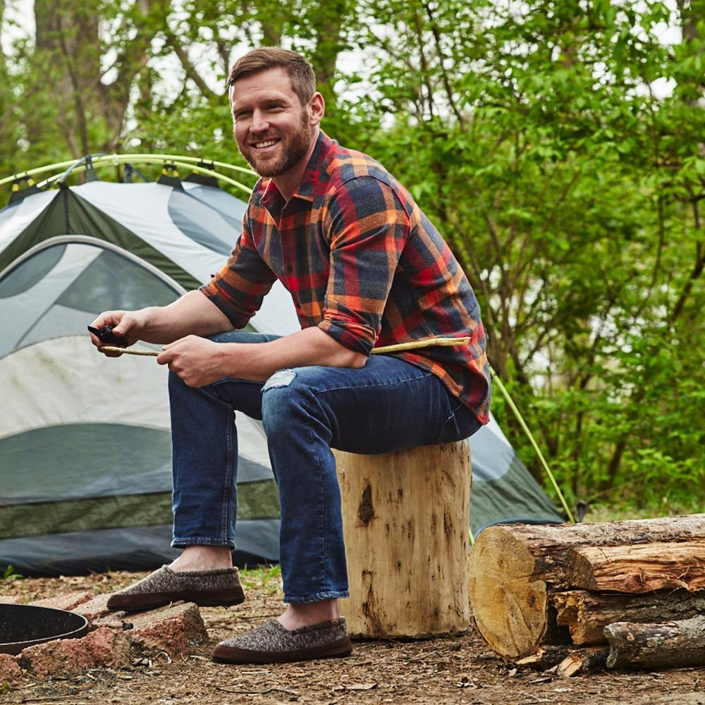 Men's Original Acorn Moccasins in Brown Tweed on Model Sitting on Stump at Campsite