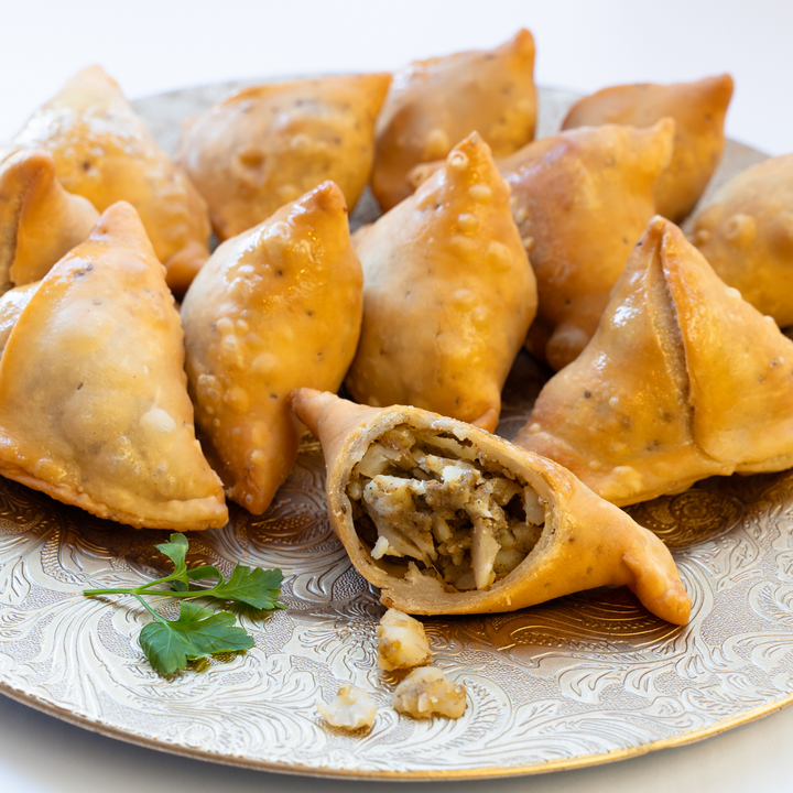 A plate of samosas, showing the filling.