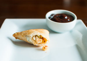 opened samosa with dipping sauce