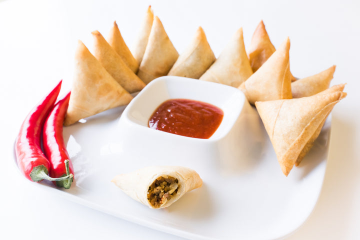 Samosas around a dipping bowl with a red pepper