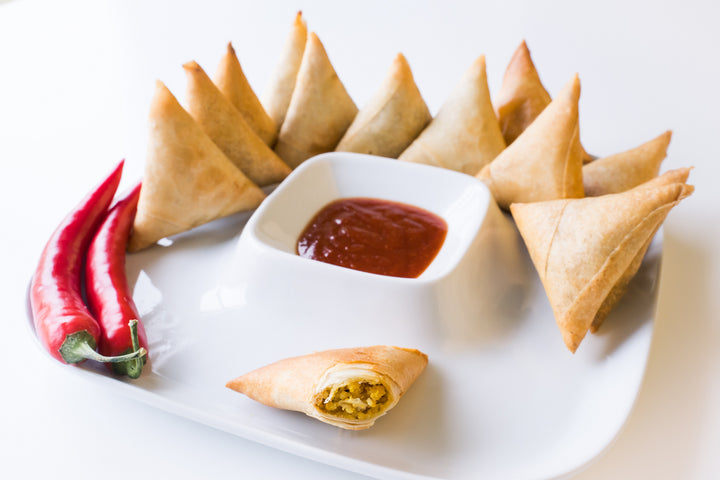 Samosas with dipping sauce and a red pepper