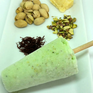 Green pista kulfi beside pistachios, saffron and cream