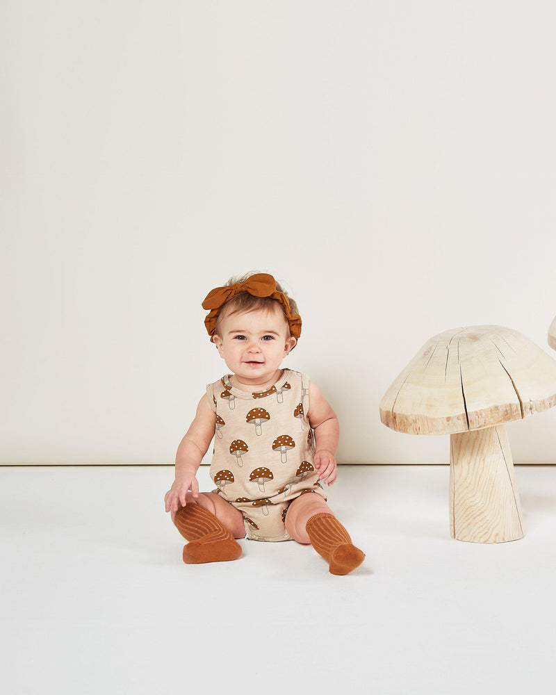 Baby in Rylee + Cru Enchanted Forest Autumn  2020 mushroom bubble romper onesie and cinnamon headband and knee socks