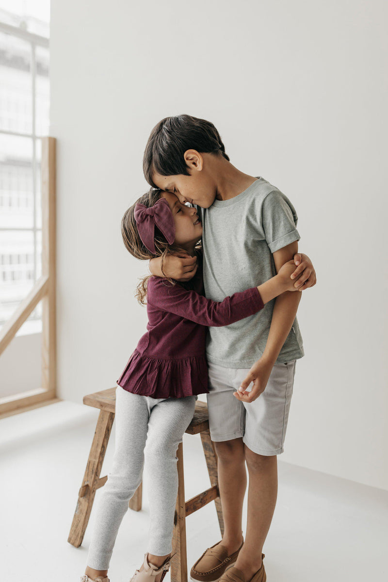 Lifestyle photo for Jamie Kay clothing - little girl wearing Plum Bailey long sleeve top and oatmeal marle essential leggings hugging brother wearing Norway Sam tee while sitting on wooden stool in studio.