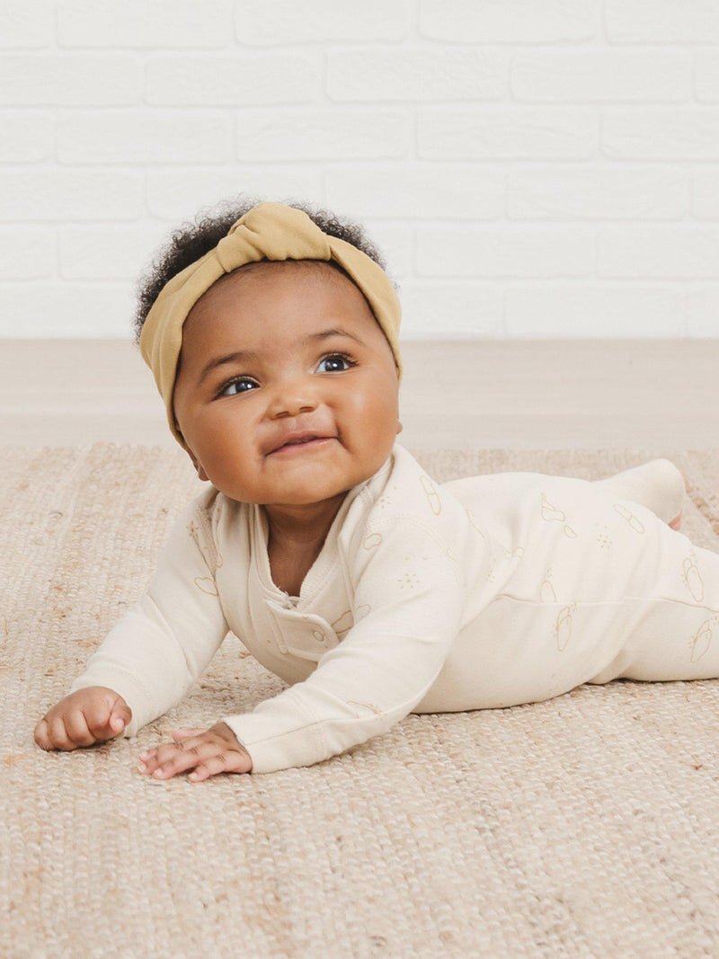 Quincy Mae Spring Summer 2021 Drop 1 arrives Friday, May 14. Photo is of a baby girl laying on her stomach smiling up at the camera wearing the gold headband and the new zipper sleeper in the clouds print.