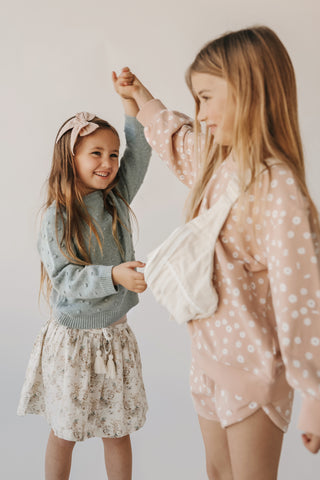 Sale on Jamie Kay - wanderlust collection pieces like Angel Corduroy Dress and Esme Floral Hazel skirt now 20% off at Barn Chic Boutique - girls wearing Jamie Kay outfits while holding hands in a studio