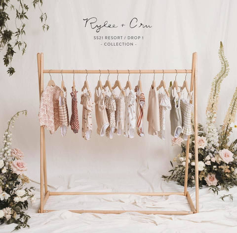 Rylee + Cru Resort Collection Spring Summer 2021 Drop 1 preview photo - clothing rack of swim and apparel coming in this collection, in a room with floral accents