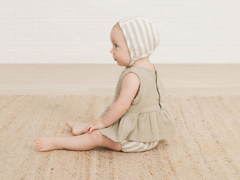 Baby girl sitting up wearing the new Quincy Mae SS21 peplum set in sage stripe and the sage stripe bonnet.