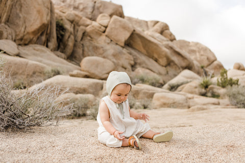 Briar Baby Linen Bonnet in sand on baby on beach with desert rocks behind - lifestyle shot of the bonnet