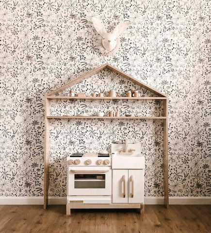 Lifestyle image of Milton & Goose play kitchen and house shelf by Kelli Murray with floral wallpaper background. Solid wood and non-toxic play kitchens for children available at Barn Chic Boutique.