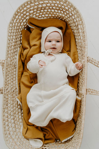 Fin & Vince Chapter 3 Solid Essentials collection - baby in bassinet wearing milk layette bonnet and sleep sack