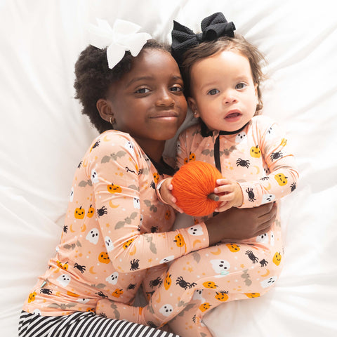 An older girl laying on a bed snuggling a baby - older girl is wearing the Macaron + Me Halloween print pajamas and the baby is wearing the footies in the same print, holding a pumpkin. Both girls are wearing bows.