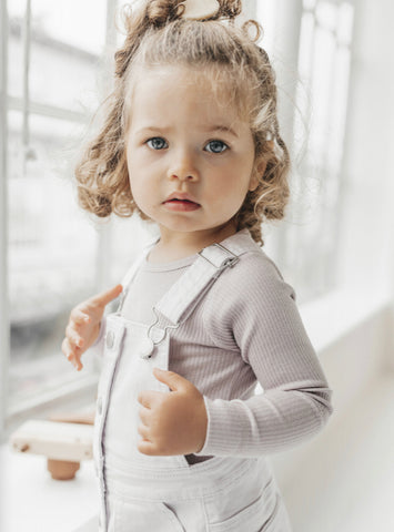 Toddler wearing Soft Lilac Corduroy Dress overalls and new Jamie Kay Flourish Collection hair clip